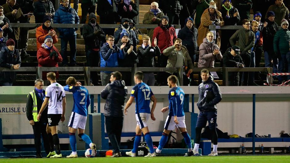 Fans watch as the players walk off at half-time during the Sky Bet League Two match at the Brunton Park, Carlisle.