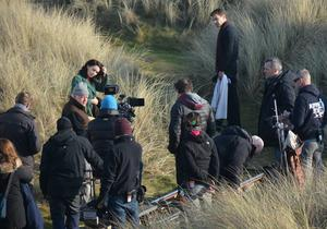 """Director Jim Sheridan films the movie adaptation of Sebastian Barry's """"The Secret Scripture"""" with actors Rooney Mara & Theo James in the sand dunes of a coastal location in North Dublin, Dublin, Ireland - 22.01.15. Pictures: Cathal Burke / VIPIRELAND.COM *** Local Caption *** Jim Sheridan with Rooney Mara & Theo James"""