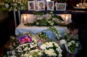 Portraits of (L-R) Jenny Loh, her mother Tan Siew Poh and Popo Fan, who were victims of the Malaysia Airlines Flight MH17 plane crash, are seen as a man lays flowers during a silent march held in their memory outside the restaurant, which Loh and Fan owned, in Rotterdam