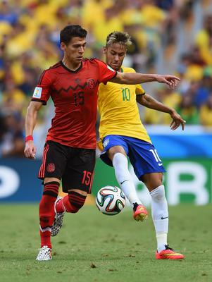 Hector Moreno of Mexico is challenged by Neymar of Brazil during the 2014 FIFA World Cup Brazil Group A match between Brazil and Mexico