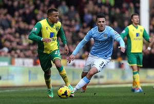 Norwich City's Martin Olsson and Manchester City's Stevan Jovetic battle for the ball