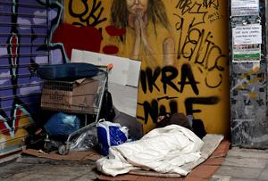 A homeless man sleeps in the streets of Athens as talks over Greek debt are on a knife-edge