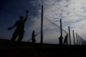 """Hungarian soldiers work on a fence that is being built at the border with Croatia, near the village of Beremend, Hungary, Tuesday, Sept. 22, 2015. Hungary's prime minister Viktor Orban said that millions of migrants are """"laying siege"""" to the borders of his country and of Europe, putting the continent in danger. (AP Photo/Petr David Josek)"""