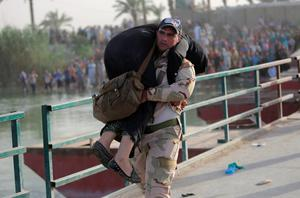An Iraqi soldier carries a displaced woman to help her cross the bridge at the outskirts of Baghdad May 19, 2015. REUTERS/Stringer