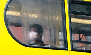 A person wearing a protective face mask sits on a bus in Dublin. Photo: Brian Lawless/PA Wire