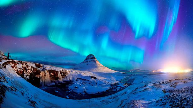 The Northern Lights appear over Kirkjufell mountain.