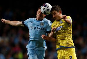 Manchester City midfielder James Milner and Sheffield Wednesday's Lewis Buxton challenge for a header during the Capital One Cup game at the Etihad. Photo: REUTERS/Andrew Yates