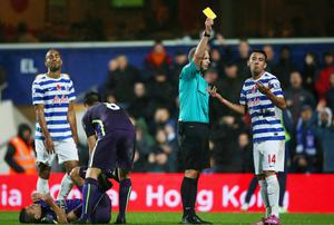 Mauricio Isla of QPR reacts as he is shown a yellow card by referee Mike Dean