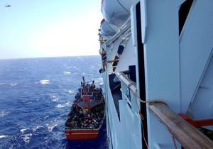 This Thursday, Sept. 25, 2014 photo taken from a cruise ship that rescued the migrants from a small boat stranded off the east Mediterranean island's main Limassol port, Cyprus, shows apparent refugees on the boat. (AP Photo/Haris Milonas)