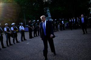 On his own: Donald Trump walks back to the White House escorted by the Secret Service. Picture: AFP/Getty