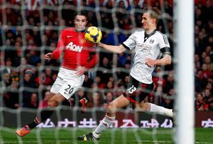 Fulham's Dan Burn (R) appears to handle the ball in the penalty box after a header on goal from Manchester United's Robin van Persie