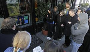 Members of the public watch former Finance Minister Brian Lenihan deliver the government's four year Budget Blueprint on a TV screen in the window of Foleys pub in Dublin city centre in 2010