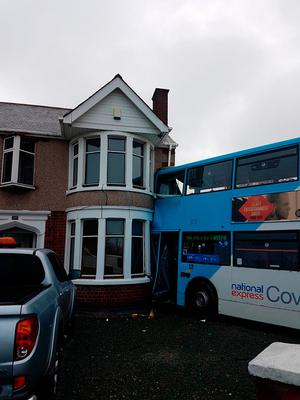 Undated West Midlands Ambulance Service handout photo of a double-decker bus which smashed into the side of a house after colliding with a 4x4 in Coventry Credit: West Midlands Ambulance Service/PA Wire