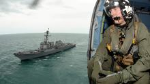 In this Tuesday, Jan. 6, 2015, photo provided by the U.S. Navy, Naval aircrewman 2nd Class Cody Witherspoon helps in the search for missing AirAsia Flight 8501 in the Java Sea, as his helicopter returns to the USS Sampson. (AP Photo/U.S. Navy, Petty Officer 1st Class Brett Cote)