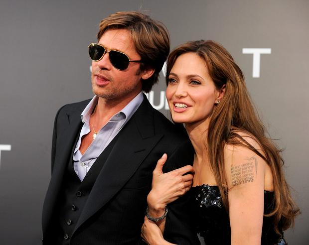 """Actor Brad Pitt (L) and actress Angelina Jolie arrive at the premiere of Sony Pictures' """"Salt"""" at Grauman's Chinese Theatre on July 19, 2010 in Hollywood, California.  (Photo by Kevin Winter/Getty Images)"""