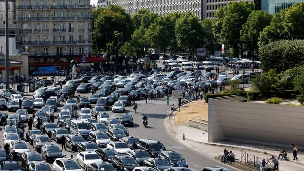 French taxi drivers, who are on strike, demonstrate at Porte Maillot to block the traffic on the Paris ring road during a national protest against car-sharing service Uber, in Paris, France, June 25, 2015. French taxi drivers stepped up protests against U.S. online cab service UberPOP on Thursday, blocking road access to airports and train stations in Paris and other cities. REUTERS/Charles Platiau