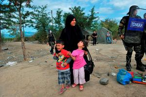 A migrant woman with children waits to pass the Greek-Macedonian border, guarded by Macedonian police near the town of Idomeni, northern Greece, on August 21, 2015. Macedonian police have reinforced control at the border with Greece in a bid to stop the influx of migrants, but a few hundred Syrians managed to cross the frontier overnight into August 21. Police prevented reporters to access a no-man's land where on August 20, officers had been in a standoff with about 1,500 migrants and refugees who wanted to cross into Macedonia. AFP PHOTO /SAKIS MITROLIDISSAKIS MITROLIDIS/AFP/Getty Images
