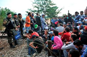 Migrants wait to pass the Greek-Macedonian border, guarded by Macedonian police near the town of Idomeni, northern Greece, on August 21, 2015. Macedonian police have reinforced control at the border with Greece in a bid to stop the influx of migrants, but a few hundred Syrians managed to cross the frontier overnight into August 21. Police prevented reporters to access a no-man's land where on August 20, officers had been in a standoff with about 1,500 migrants and refugees who wanted to cross into Macedonia. AFP PHOTO /SAKIS MITROLIDISSAKIS MITROLIDIS/AFP/Getty Images