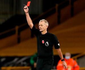 Referee Martin Atkinson shows a red card to Crystal Palace's Luka Milivojevic (not in picture) after checking the pitch-side monitor. Photo: PA