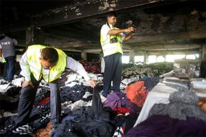 Members of the Criminal Investigation Department (CID) inspect the factory belonging to Tung Hai Group, a large garment exporter, after the fire