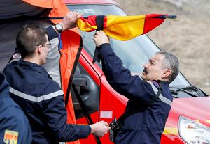 French firefighters install a black ribbon on a Spanish flag outside a tent where relatives and officials are due to pay tribute to the victims of the Airbus A320 crash, outside Le Vernet near Seyne-les-Alpes, March 25, 2015. REUTERS/Robert Pratta