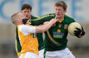 Meath's Kevin Reilly attempts to brush off Antrim's Paddy Cunningham during yesterday's clash at Casement Park