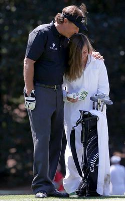 Phil Mickelson of the U.S. kisses his daughter on the first hole of the annual Par 3 contest. Photo: Reuters