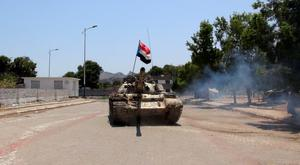 An army tank moves on a street in Yemen's southern port city of Aden