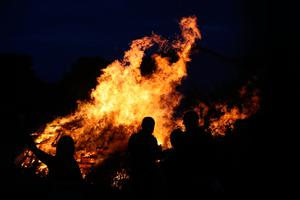 People watch a bonfire on Belfast's Shankill Road as bonfires were set to be lit at midnight, as part of a loyalist tradition to mark the anniversary of the Protestant King William's victory over the Catholic King James at the Battle of the Boyne in 1690. Photo credit: Niall Carson/PA Wire