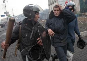 Anti-government protesters detain a wounded policeman (C) during clashes in the Independence Square in Kiev