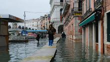 People walk in a flooded street during a period of seasonal high water in Venice. Photo: Reuters/Manuel Silvestri