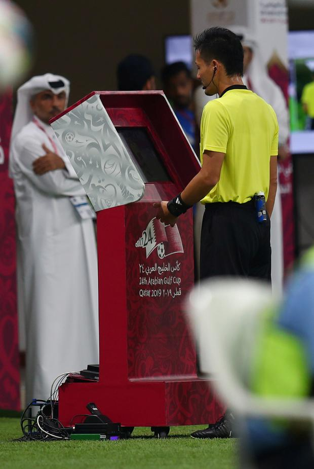 A referee consults with VAR using a pitch-side monitor