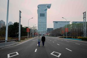A man and a boy wearing facemasks amid concerns of coronavirus walk on a road towards the Olympic park in Beijing (Photo by NICOLAS ASFOURI/AFP via Getty Images)