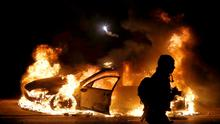 A police car burns on the street after a grand jury returned no indictment in the shooting of Michael Brown in Ferguson, Missouri. Gunshots were heard and bottles were thrown as anger rippled through a crowd outside the Ferguson Police Department in suburban St. Louis after authorities on Monday announced that a grand jury voted not to indict a white officer in the August shooting death of an unarmed black teen (REUTERS/Jim Young)