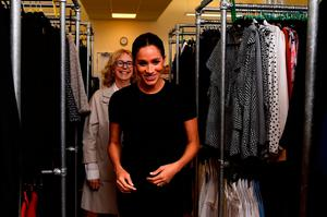 Britain's Meghan, the Duchess of Sussex (R), walks through clothes racks with Chair of Smart Works Lady Juliet Hughes-Hallett (L) during her visit to Smart Works, a charity to which she has become patron, at St Charles hospital in west London on January 10, 2019. (Photo by CLODAGH KILCOYNE / POOL / AFP)
