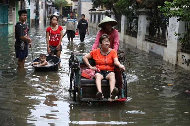 A woman rides a tricycle on a flooded street in Jakarta, Indonesia (AP Photo/Dita Alangkara)