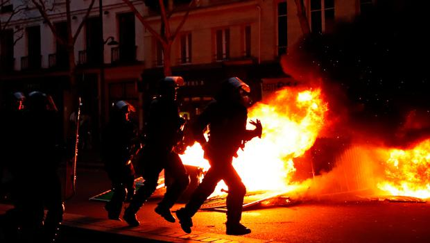 """Riot policemen run near a fire during a demonstration by the """"yellow vests"""" movement at Boulevard Saint Germain in Paris, France, January 5, 2019. REUTERS/Gonzalo Fuentes"""