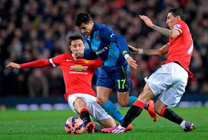Arsenal's Alexis Sanchez gets through the challenges of Manchester United duo Ander Herrera and Angel Di Maria during the FA Cup quarter-final at Old Trafford. Photo: OLI SCARFF/AFP/Getty Images