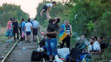 "A migrant, hoping to cross into Hungary, plays with a child along a railway track outside the village of Horgos in Serbia, towards the border it shares with Hungary, August 31, 2015. The European Union could soon fund and set up new reception facilities for asylum-seekers in Hungary as it is already doing in Italy and Greece, its migration commissioner said on Monday. Saying he would travel to Budapest soon, Dimitris Avramopoulos told reporters that the EU executive was ready to offer further help to the government as it takes in large numbers of people crossing the Balkans to reach the European Union and would ""if necessary, set up a hotspot in Hungary"". REUTERS/Marko Djurica  TPX IMAGES OF THE DAY"