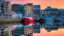 Morning view on row of buildings and fishing boats in Galway port