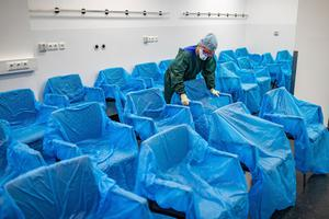 A nurse assembles plastic-wrapped chairs in a waiting area in the central emergency room of the University Hospital in Essen, Germany (Marcel Kusch/dpa via AP)