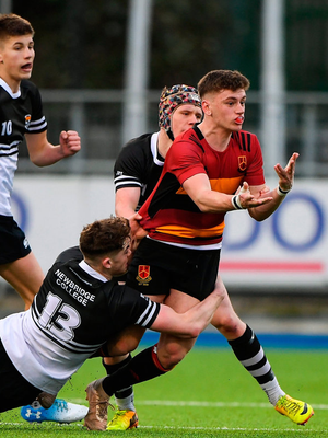 Robbie Browne of CBC Monkstown Park is tackled by Marcus Kiely of Newbridge College. Photo: Matt Browne/Sportsfile