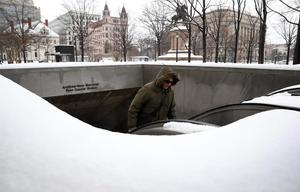 A commuter emerges from the Metro subway system after overnight and early morning snowfall in Washington