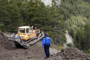 French Gendarme Bruno Hermignies stands by a bulldozer clearing a path to the crash site of the Germanwings Airbus A320 in the mountains, near Seyne-les-Alpes, French Alps, March 30, 2015.  REUTERS/Claude Paris/Pool