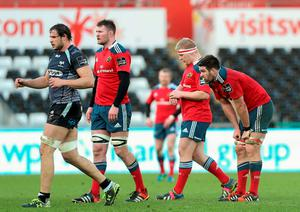 Munster players show their disappointment after their defeat to Ospreys in Swansea.
