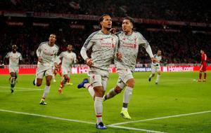 BIG MAN: Virgil van Dijk celebrates with Roberto Firmino after heading in Liverpool's crucial goal at the Allianz Arena. Pic: Reuters/Andrew Boyers