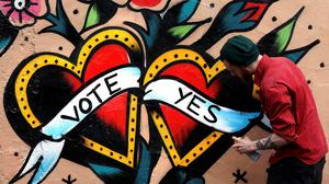 A graffiti artist finishes a Yes campaign piece in Dublin yesterday. Photo: Reuters/Cathal McNaughton