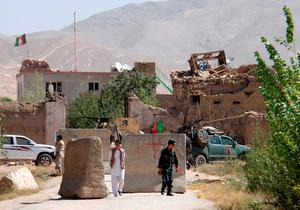 An Afghan policeman (R) walks outside a prison building after an attack in Ghazni province. Photo: Reuters