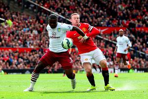 Manchester United's Wayne Rooney battles for the ball with Jores Okore of Aston Villa