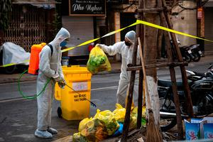 Environment workers disinfect and collect waste from the quarantined area on Truc Bach Street in Hanoi, Vietnam. Photo: Linh Pham/Getty Images